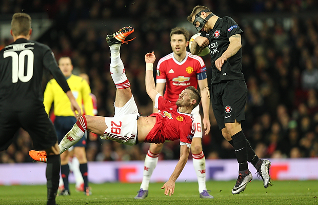 FOOTBALL: Morgan Schneiderlin of Manchester United with an overhead kick in front of Nikolay Bodurov of FC Midtjylland during the UEFA Europa League round of 32, second leg, match between Manchester United FC and FC Midtjylland at Old Trafford, Manchester, England on February 25, 2016. Photo: Claus Birch